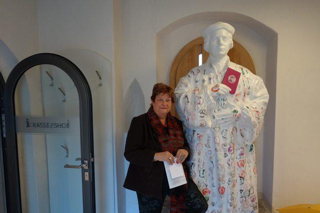 """Barbara Hackenschmidt neben der Luther-Figur mit Werbung für den """"Luther-Pass""""."""